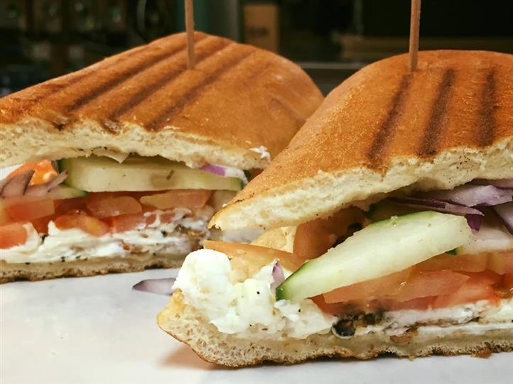 a panini with turkey, tomato, cucumber, red onion