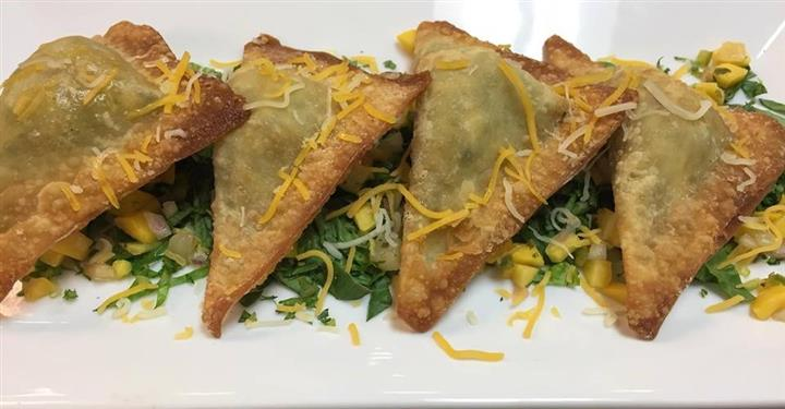 three empanadas on a plate on a bed of lettuce and corn covered in shredded cheese