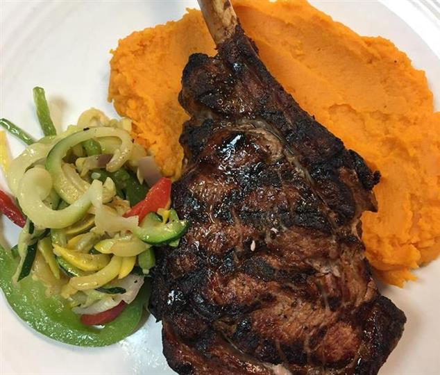 a lamb chop with a side of mixed vegetables and yams