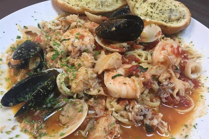 pasta with shrimp, mussels, and clams in an orange sauce with a side of garlic bread