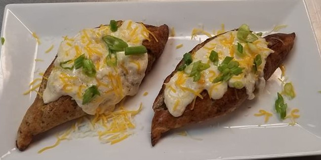 two baked potaoes with white sauce on top with cheese and scallions