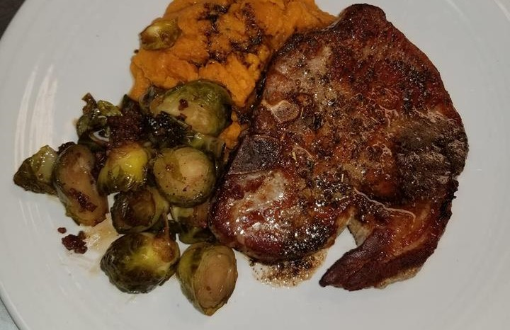 a steak with a side of halved brussel sprouts and yams