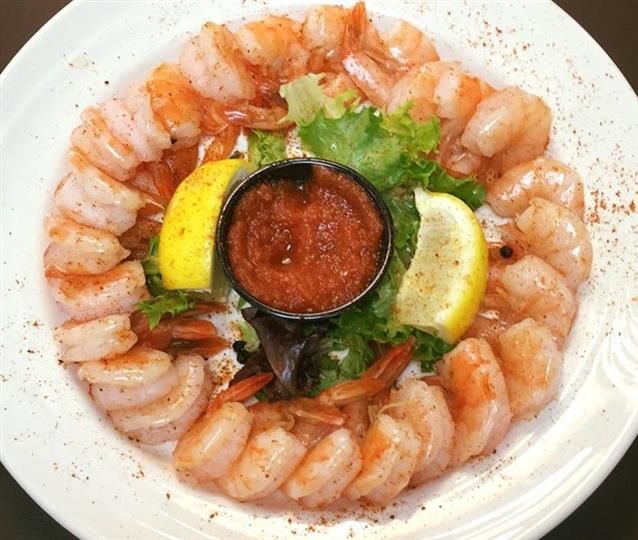 shrimp cocktail with dipping sauce and two lemon wedges