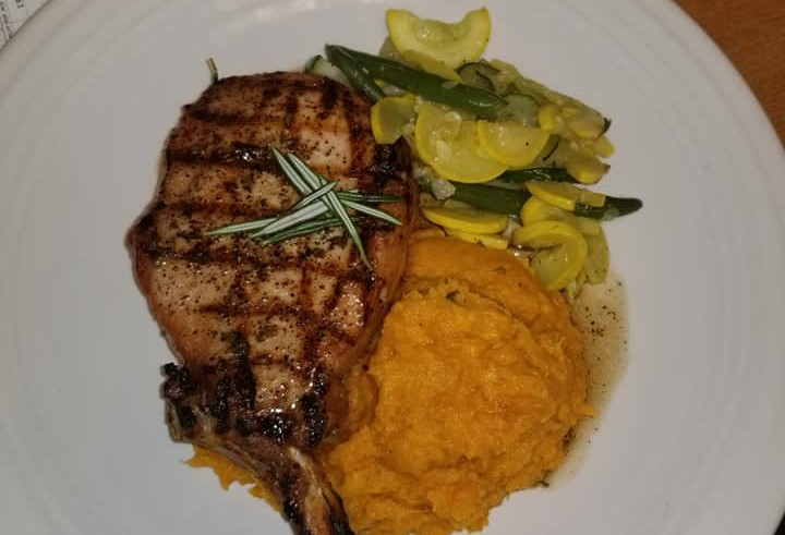 a lamb chop with a side of string beans, zucchini and yams