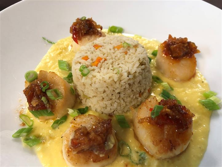 a scoop of rice surrounded by five scallops in a pool of yellow sauce