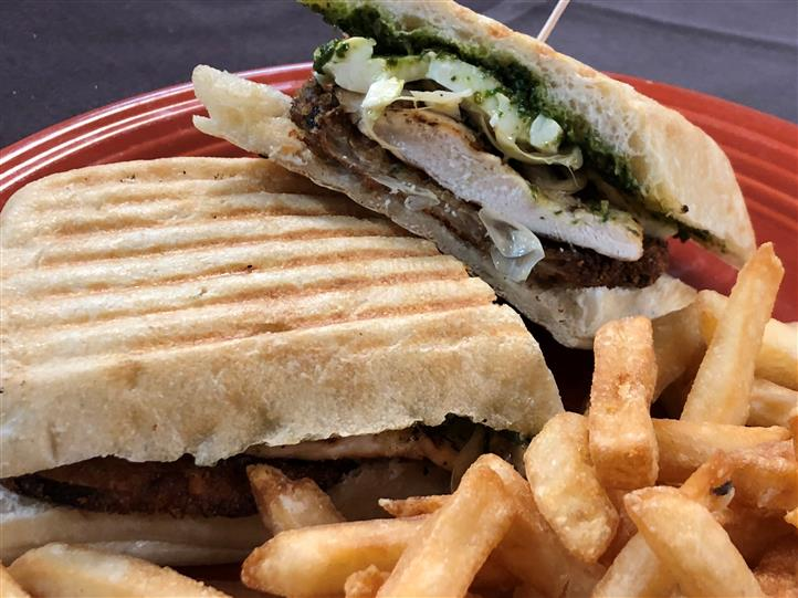 a panini with grilled chicken and pesto with a side of french fries