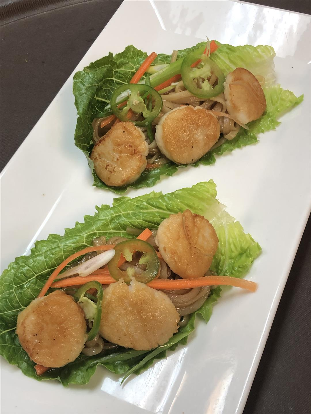 two pieces of lettuce with three scallops on each with shredded carrot and jalapeno slices