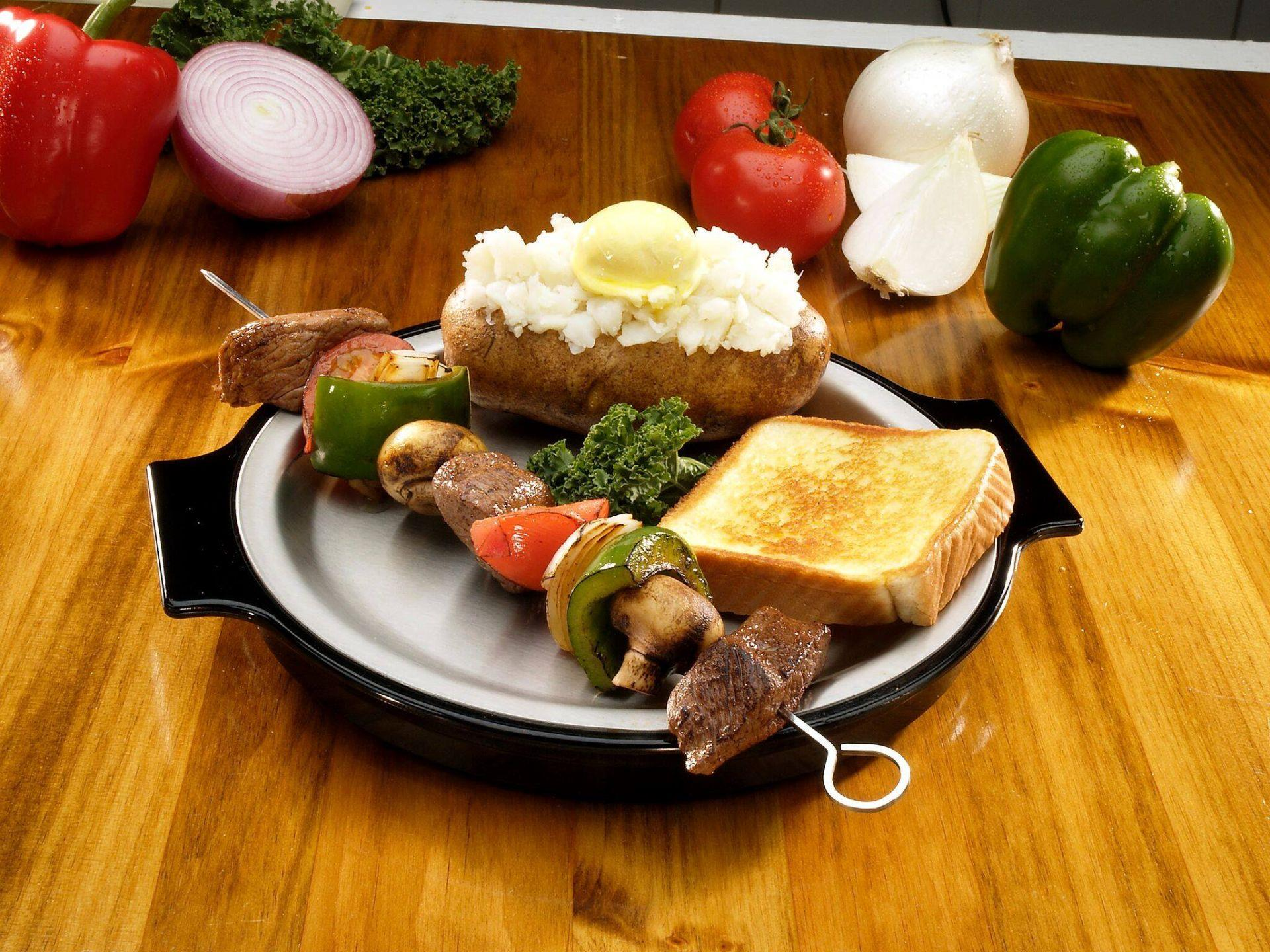 Steak and pepper skewer with baked potato and Texas toast