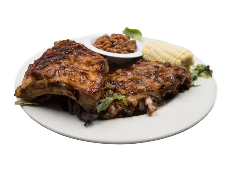 Ribs with corn on the cob on a white plate with a side of baked beans, in a white bowl also on the white plate.