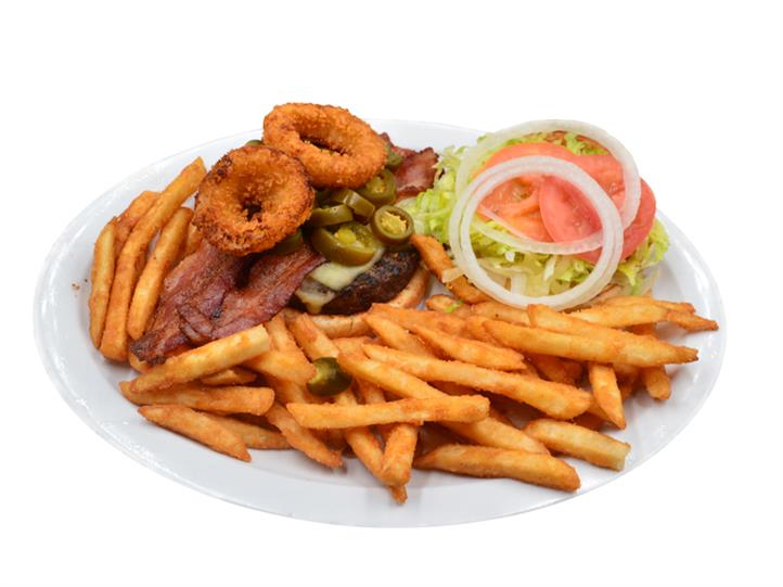 Cheeseburger with cheese, meat patty, onion rings, lettuce, tomatoe and onion pieces and bacon on a bun with a side of french fries on a white plate.