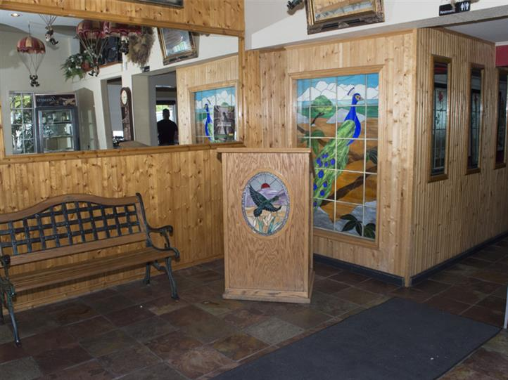 Front entrance of restaurant which consists of wood walls and tile floor. On the walls there is a mural of a peacock and a large mirror.