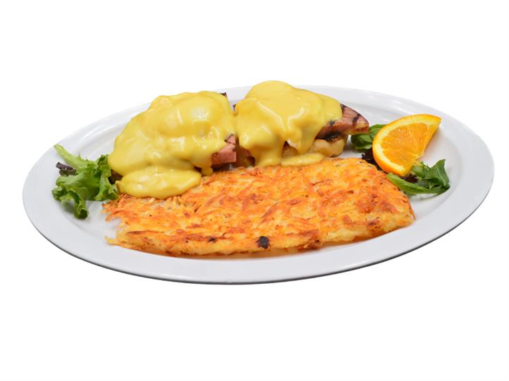 Eggs Benedict with ham covered in Hollandaise sauce with a side of hashbrowns on a white plate. Garnished with lettuce pieces and a slice of orange.