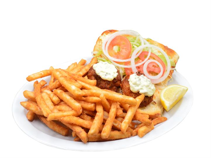 Maryland Crab Cake Sandwich which consists of two sandwiches containing a crab cake, tartar sauce, tomatoe, onion and lettuce on a bun with a side of fried on a white plate.
