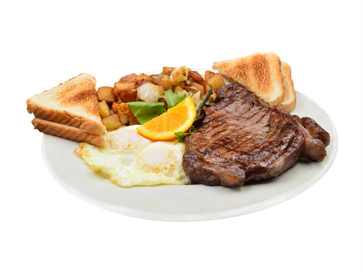 steak and over easy eggs with toast and homefries on a white plate. Garnished with lettuce pieces and a slice of orange.