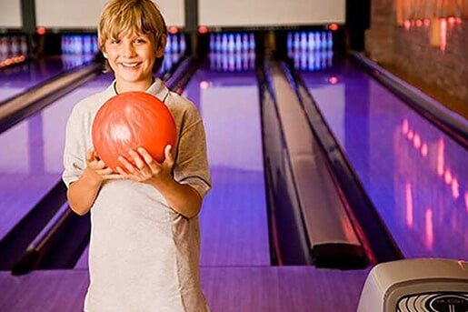 Kid holding a red bowling ball