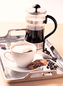 French press with cup full of coffee