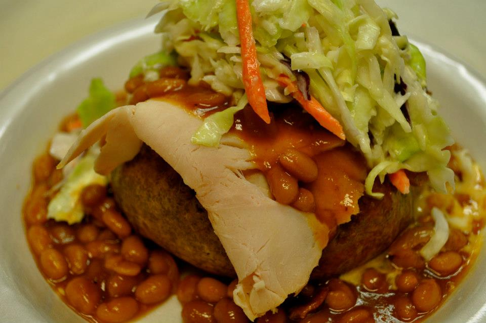 Baked potato topped with coleslaw, baked beans and turkey