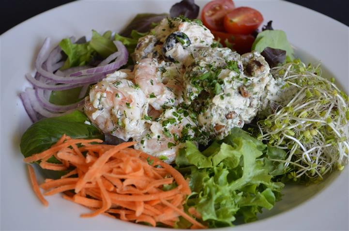 Four seasons house salad with Mixed greens, carrots, grape tomatoes, purple onions, and sprouts topped with shrimps