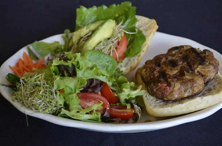 Open faced burger with mixed greens served in a white plate