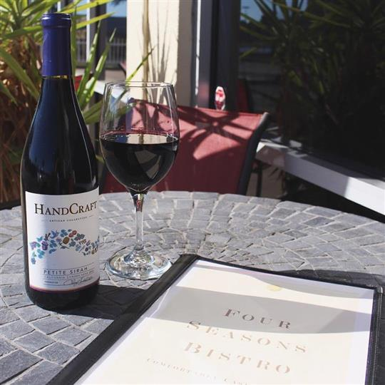 An outdoor close shot of a bottle and a glass of white wine beside the manual menu, on a stone table