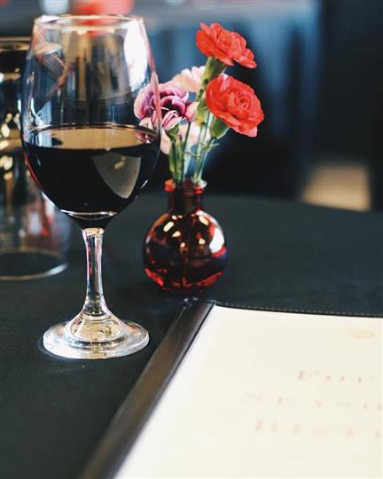 A glass of red wine beside a small red vase of flowers, and the manual menu