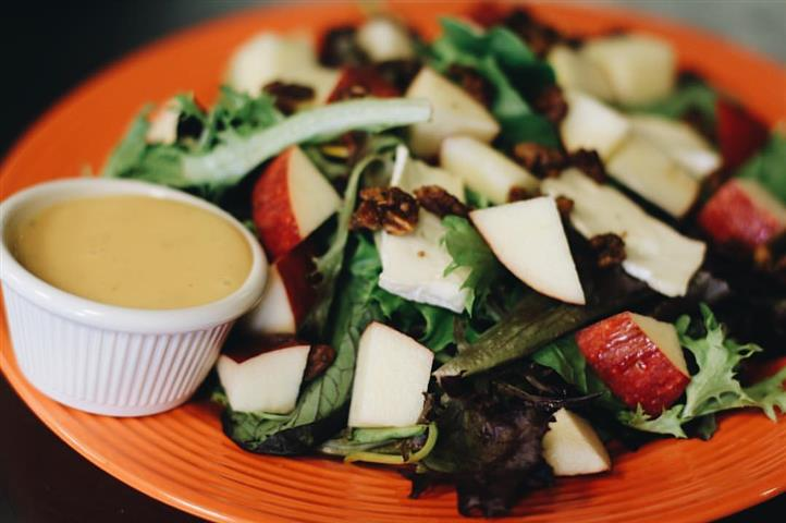 Brie and apple salad on mixed greens with candied pecans, with a bottle of white wine and a glass of white wine