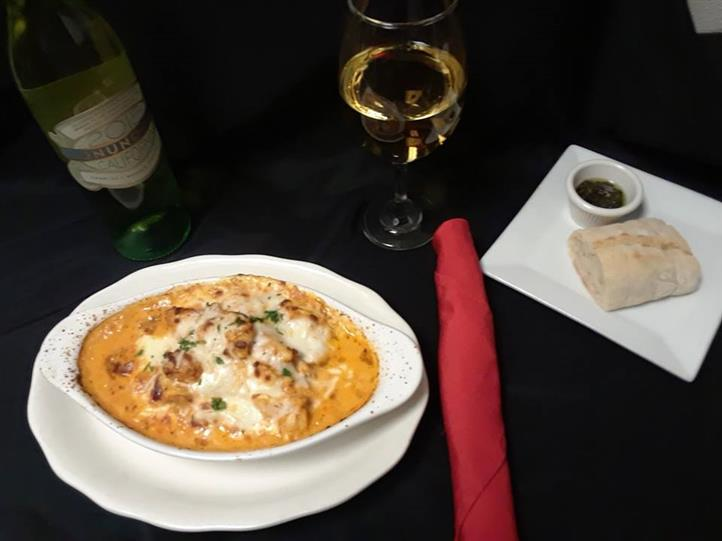 Lightly breaded shrimp fried to a crisp, golden brown and tossed in a sweet chili sauce, finished with fresh parmesan and parsley served with bread and dipping sauce, beside a bottle and a glass of white wine
