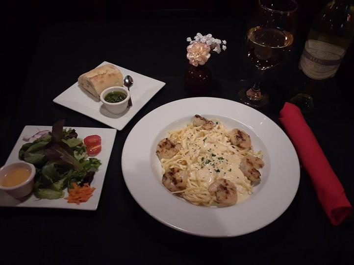 Fettuccine alfredo served with shrimps, served with side salad, white bread with dipping sauce and a glass of white wine