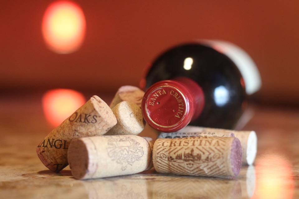 Assorted wine corks in front of a bottle of red wine