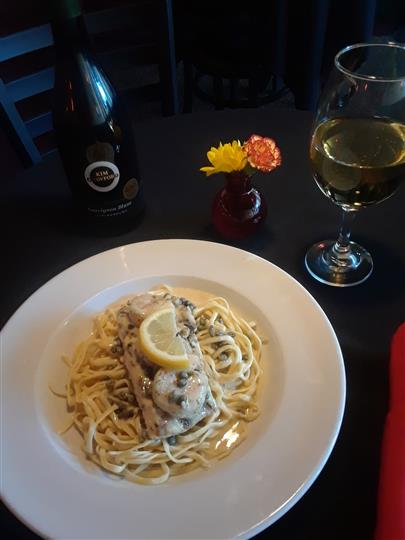 Lightly pan fried or grilled chicken breast in a lemon butter white wine sauce with capers served over linguine pasta, with a glass of white wine