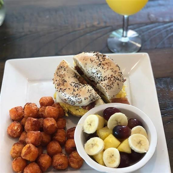 breakfast sandwich on a bagel with fruit salad, tater tots and a mimosa