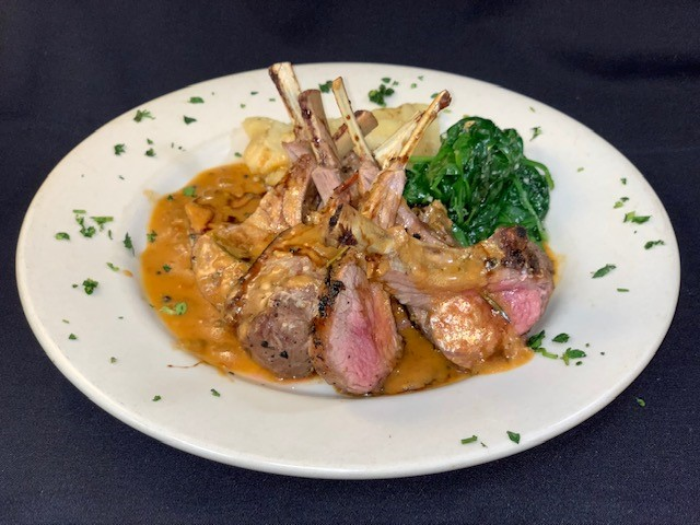 Rack of lamb served with potatoes and spinach