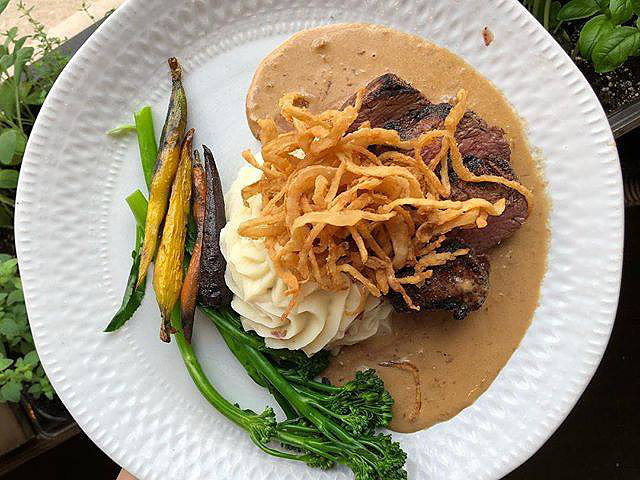 Steak served with mashed potatoes, broccolini, crispy fried onions anda special sauce