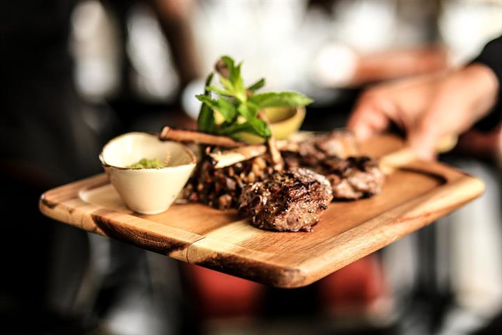 Filet mignon served on a wooden board with dipping sauce on the side