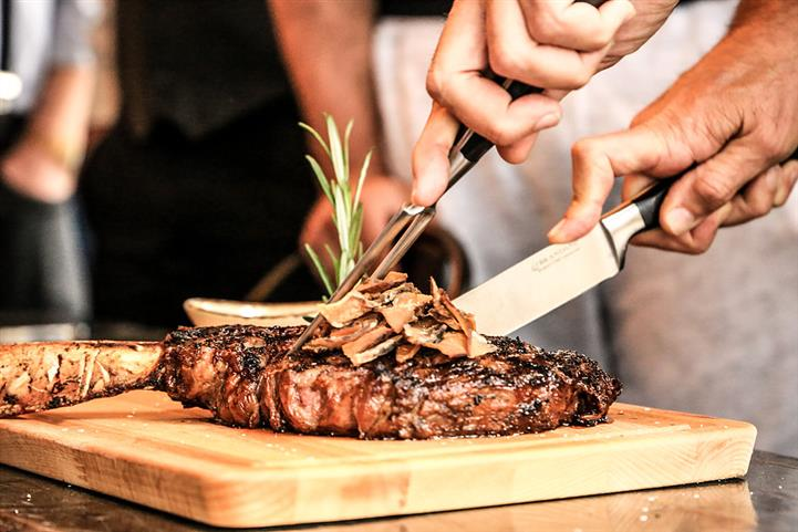 Chef Cutting a steak on a wooden cutting board