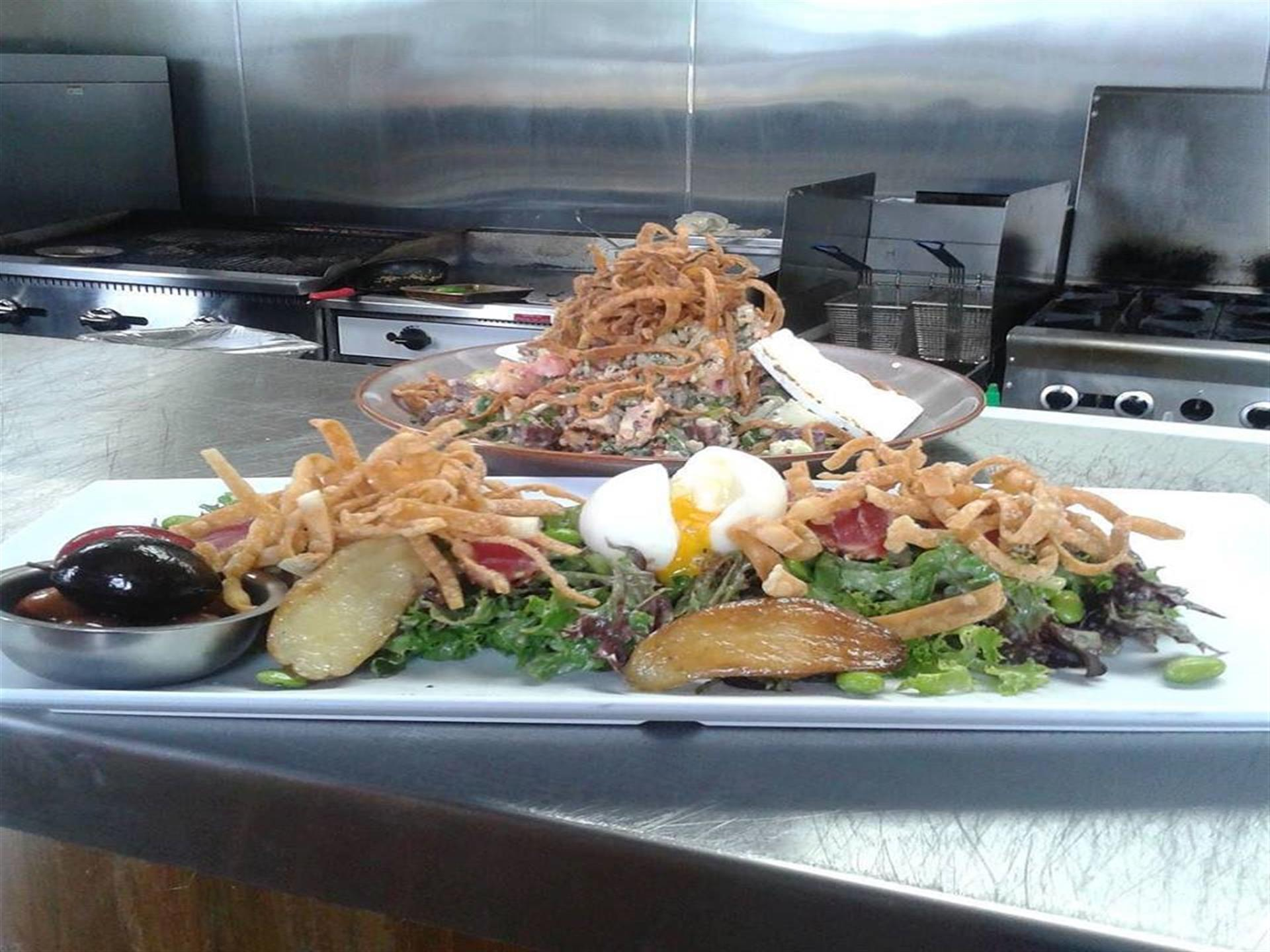 plated salad topped with fried onions and a soft boiled egg