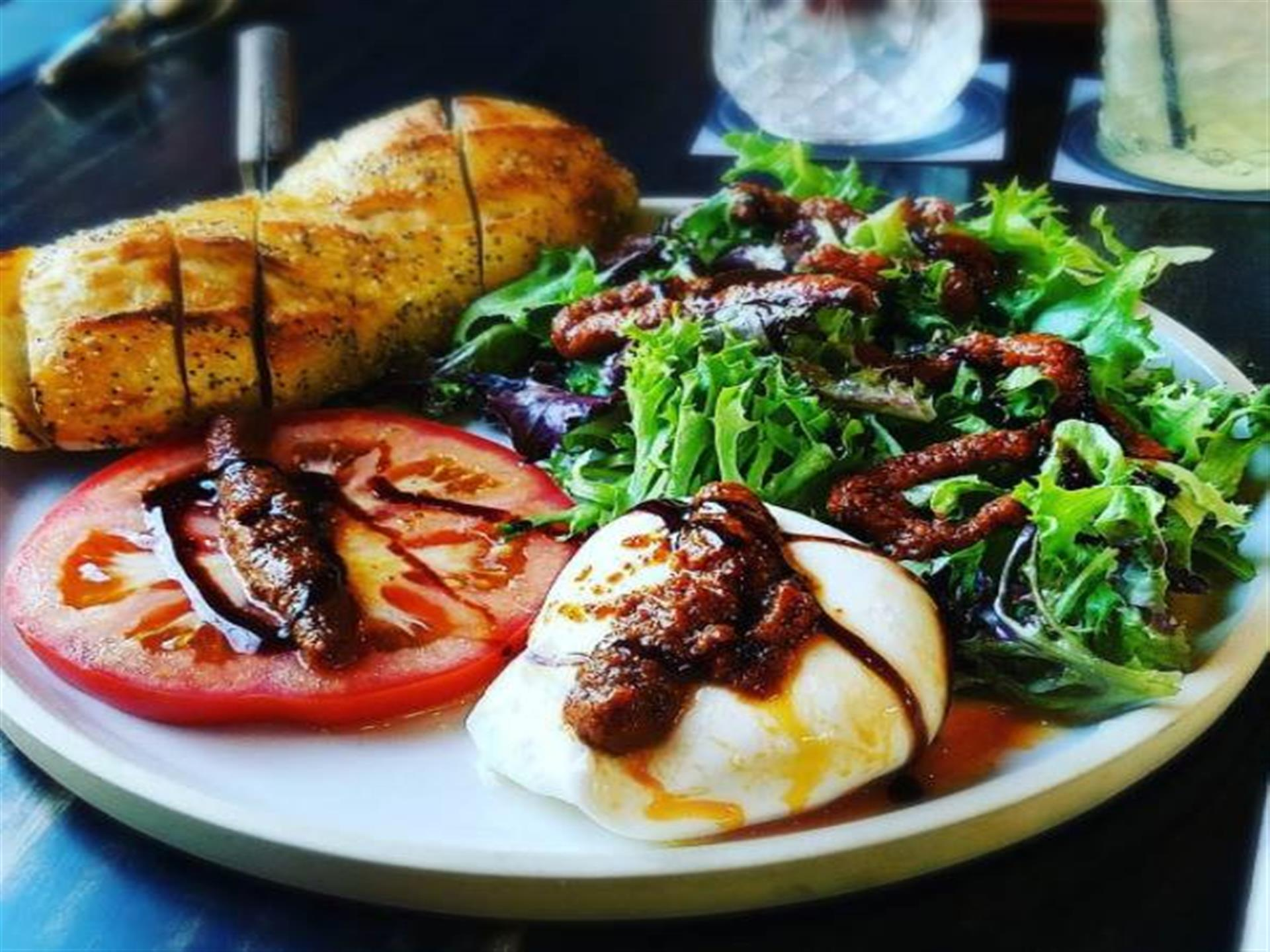 salad with sliced tomato. fresh mozzarella and load of italian bread