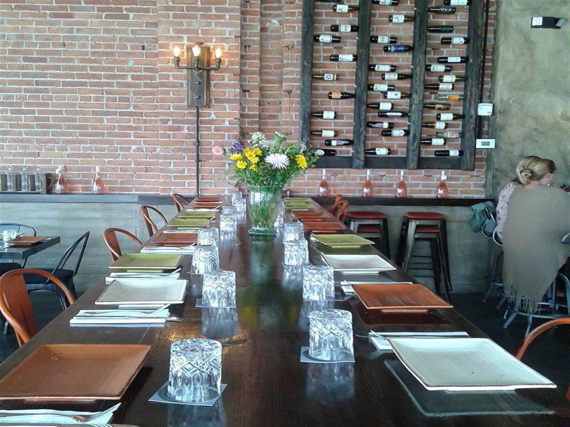 long table set in the restaurant with a wine rack in the background