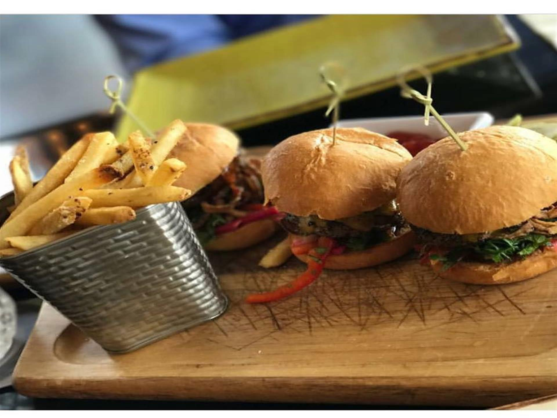 three sliders on a cutting board with french fries