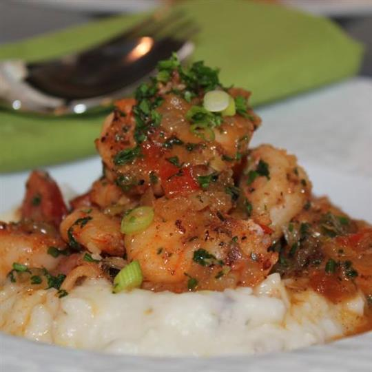 shrimp over mashed potatoes on a plate