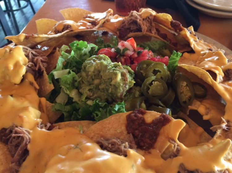 Loaded nachos with pulled pork, guacamole and jalapenos