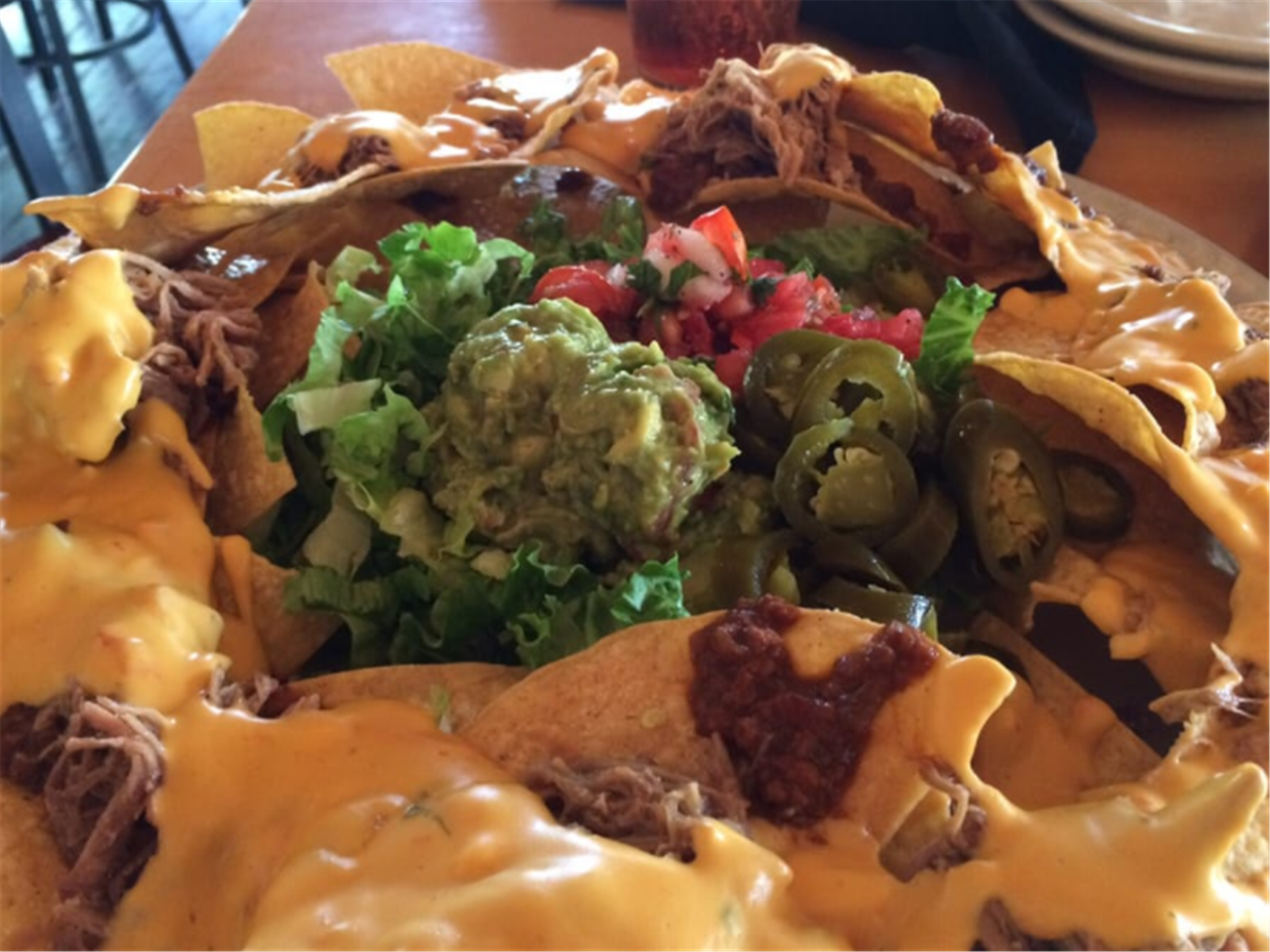 nachos topped with cheese, beans and guacamole