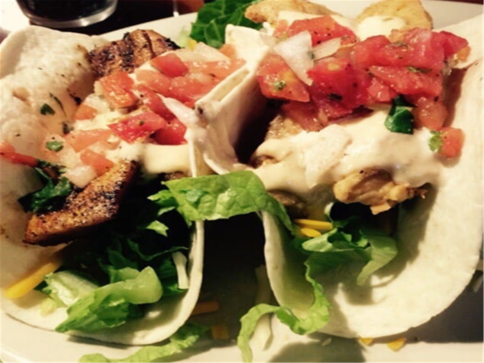 fish tacos topped with lettuce and tomatoes