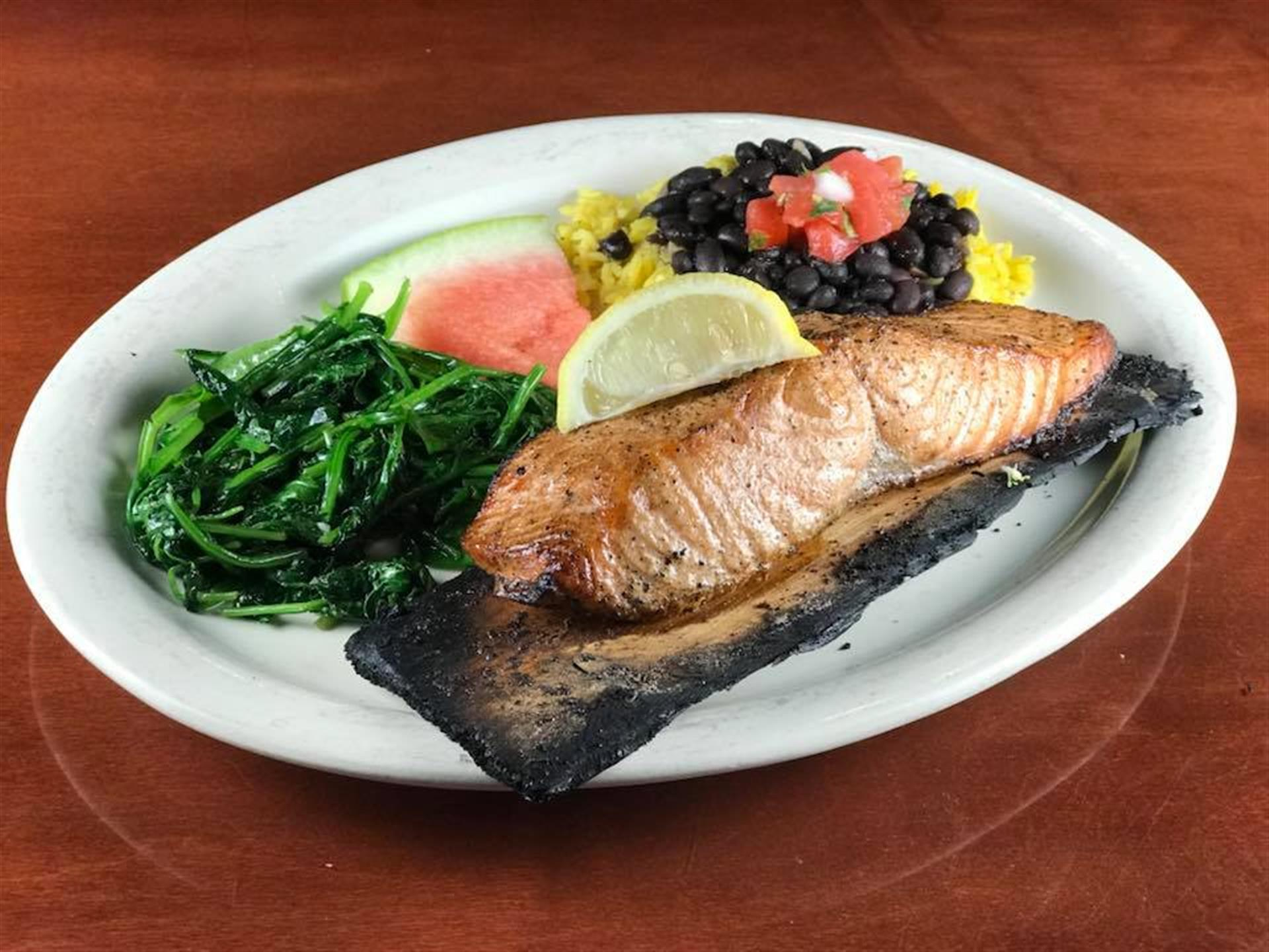 salmon cooked on cedar plank with black beans, corn, and spinach
