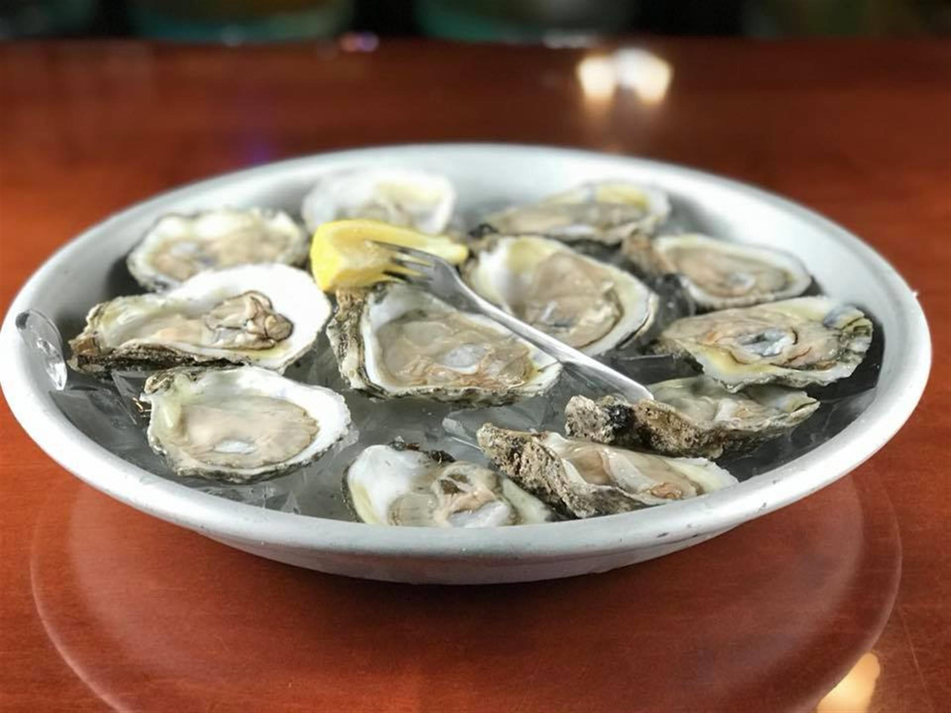 raw oysters on the half shell served with lemon on a bed of ice