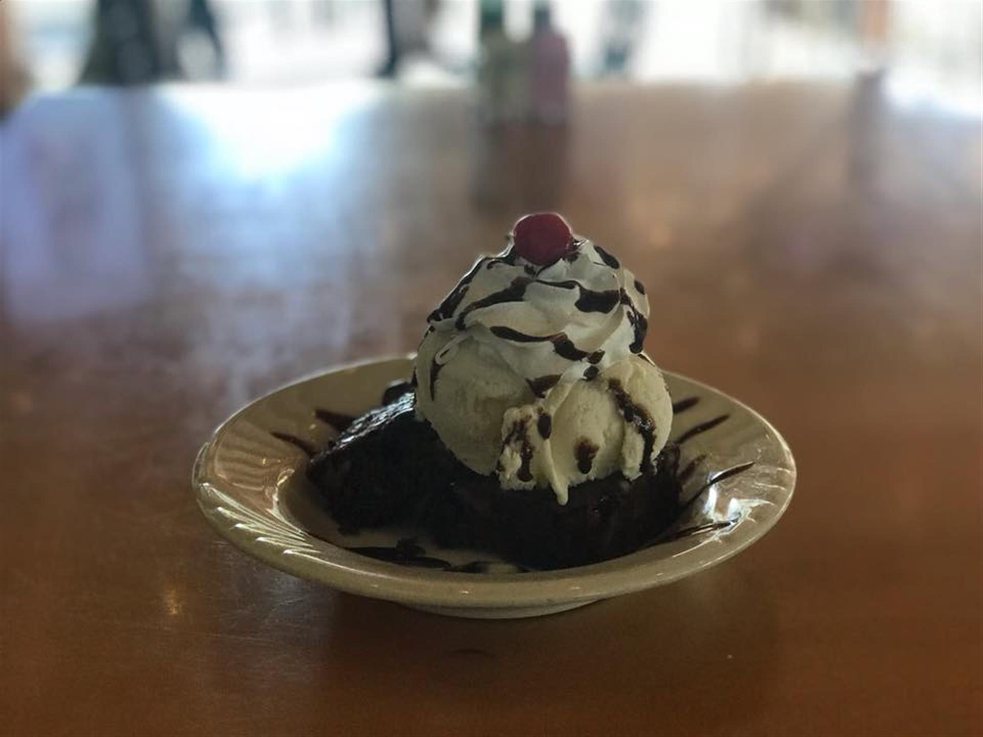 brownie topped with ice cream, whipped cream, cherry and chocolate sauce
