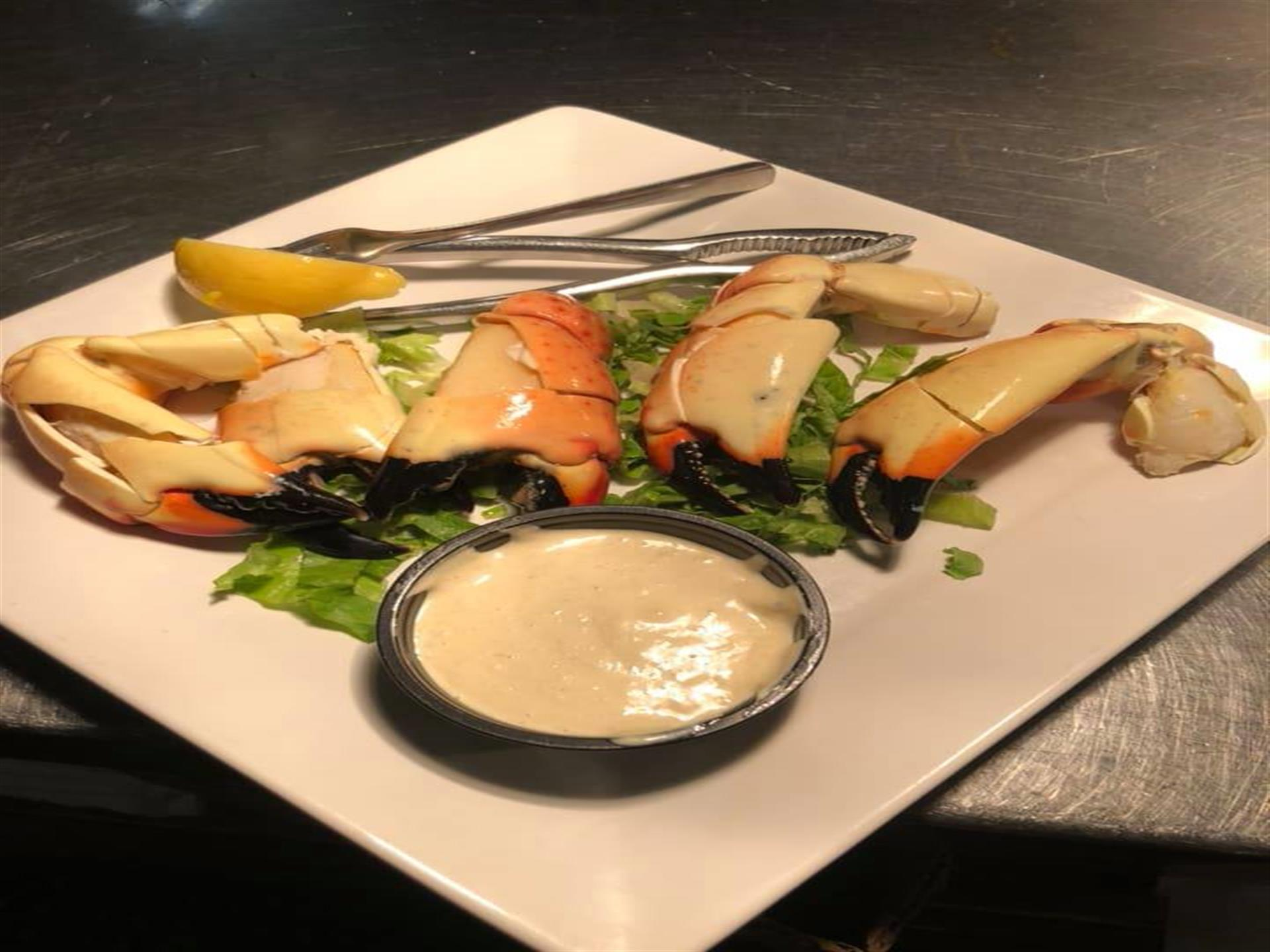 crab claws on a plate with dipping sauce