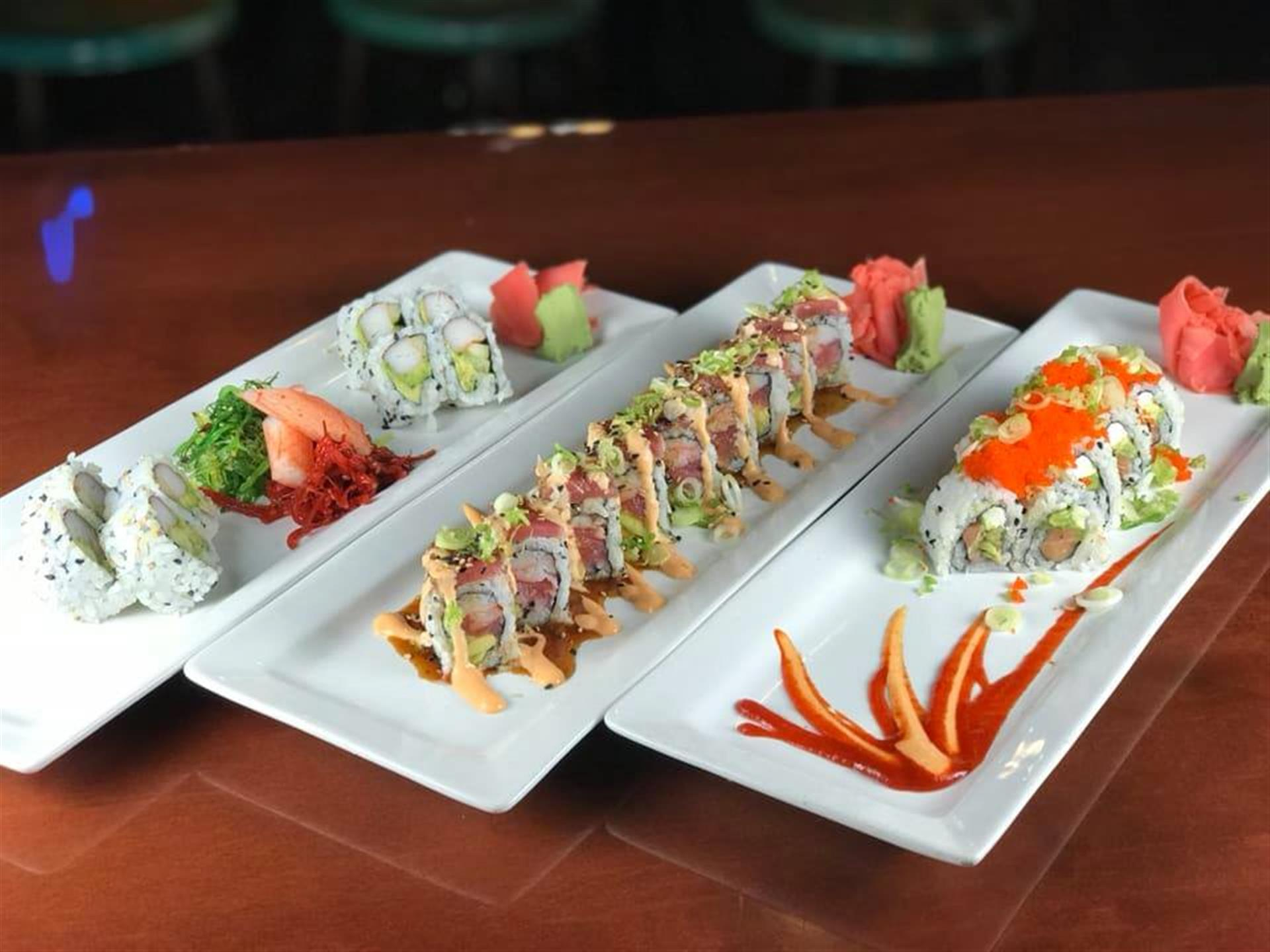 three sushi rolls on plates