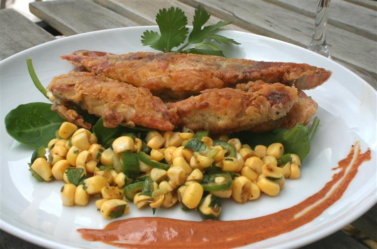 Fried soft shell crab on a white plate with corn and garnish