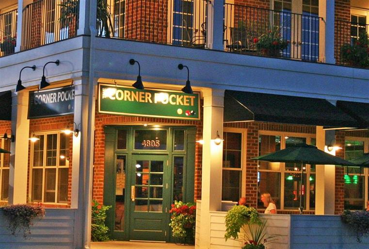 Outside of corner pocket showing a green door on a brick building with two decks